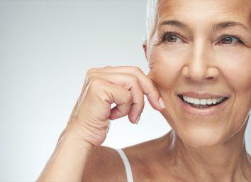 smiling Caucasian senior woman with short gray hair pinching her cheek