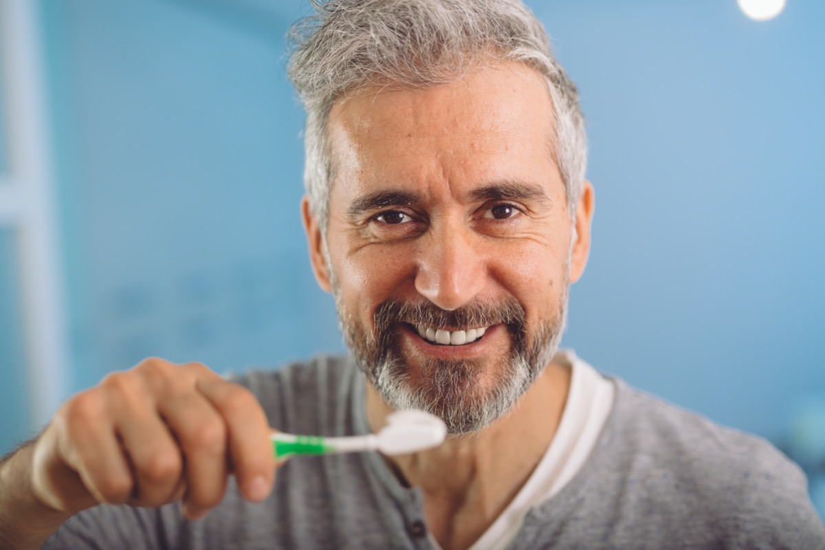 middle aged bearded gray haired man brushing his teeth