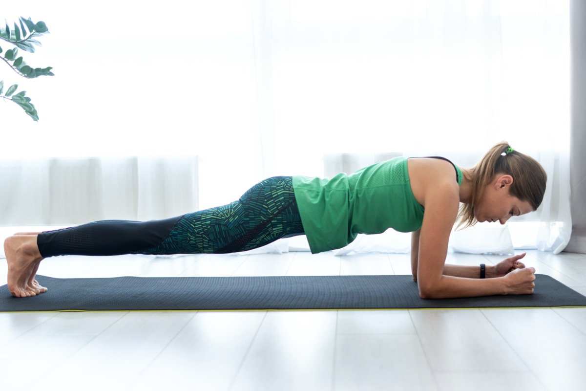Profile view of concentrated and serious young woman standing in plank pose on fitness mat, training at home