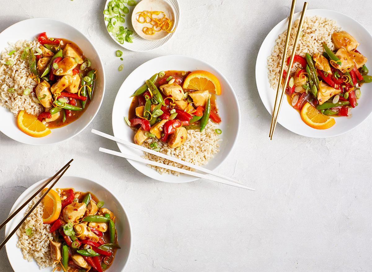 bowls of homemade orange chicken with chopsticks