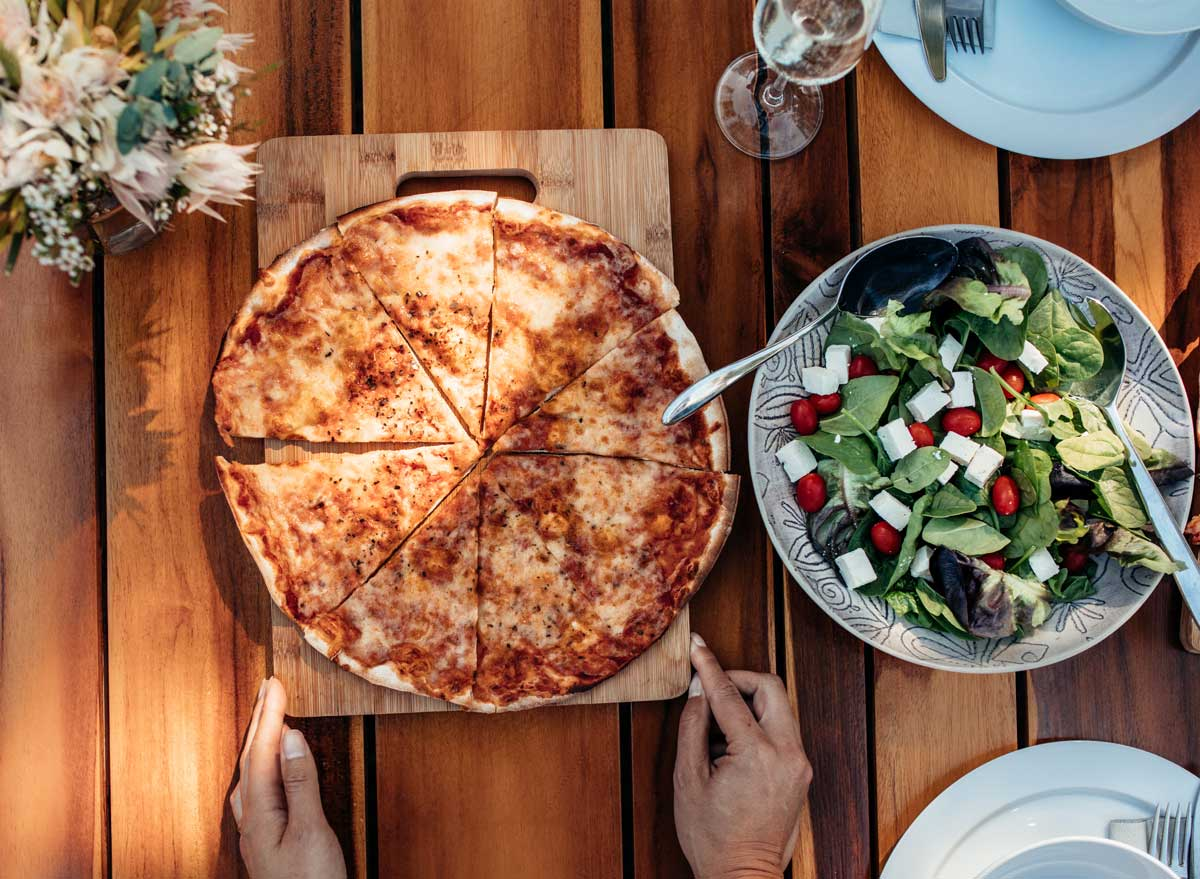 Serving pizza on table with side spinach salad