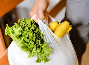 man holding plastic grocery bag with lettuce and bananas
