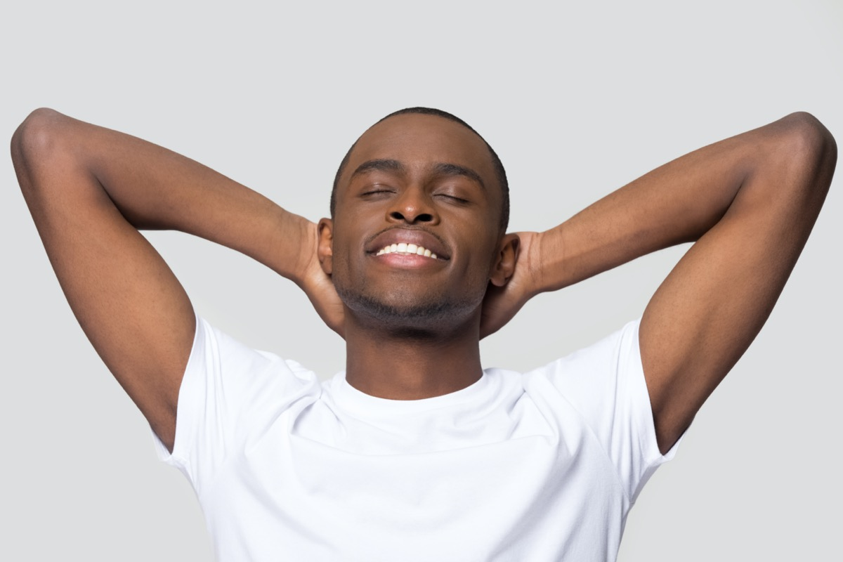 man relaxing with hands behind head, satisfied peaceful young male with closed eyes resting, enjoying free time, meditating, stretching