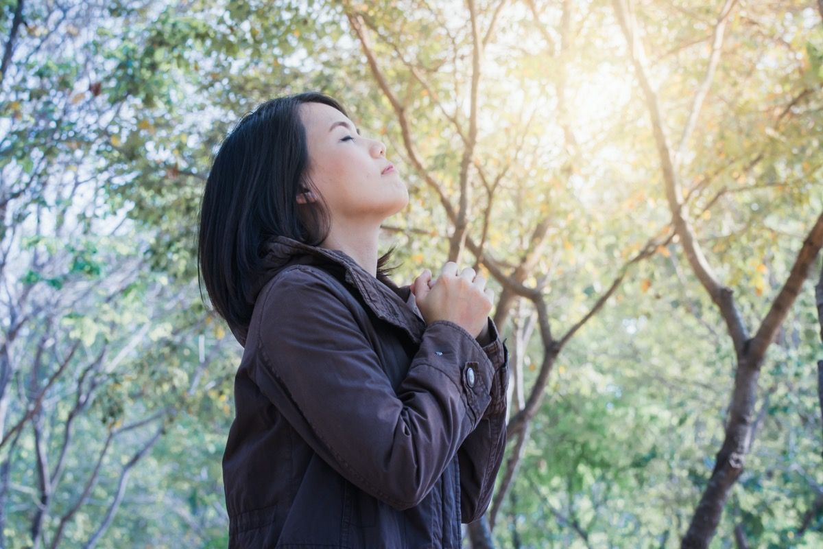 woman smiling, enjoying relaxing breathing fresh air in the garden summer sunset