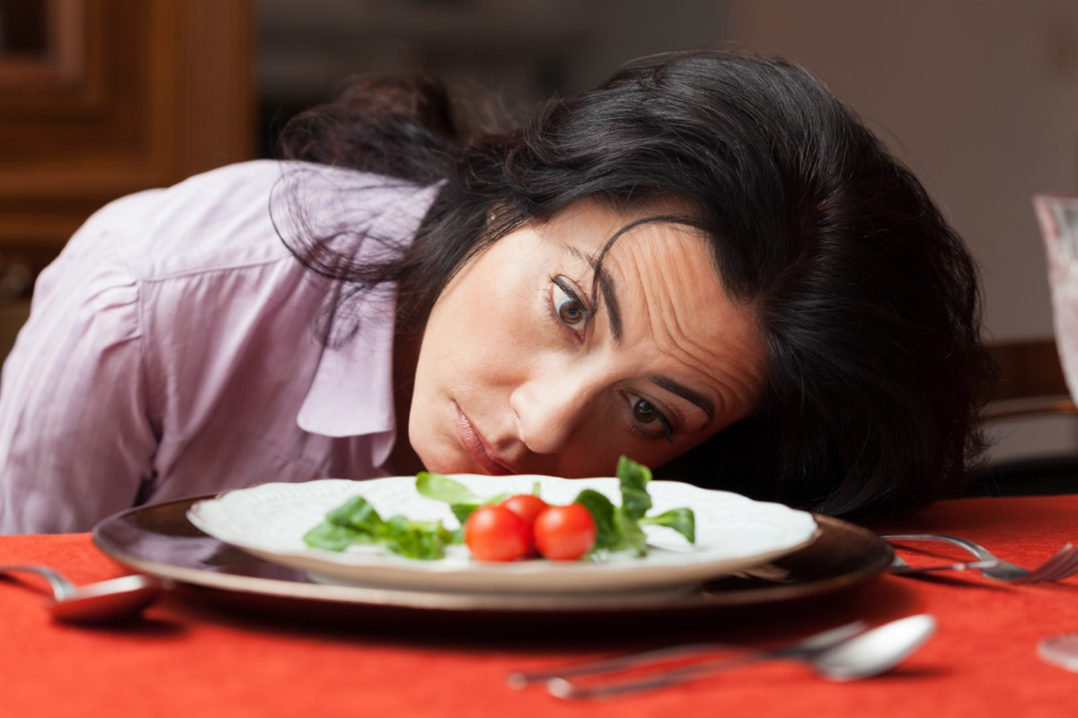 Woman looking to a little salad is tired about diet