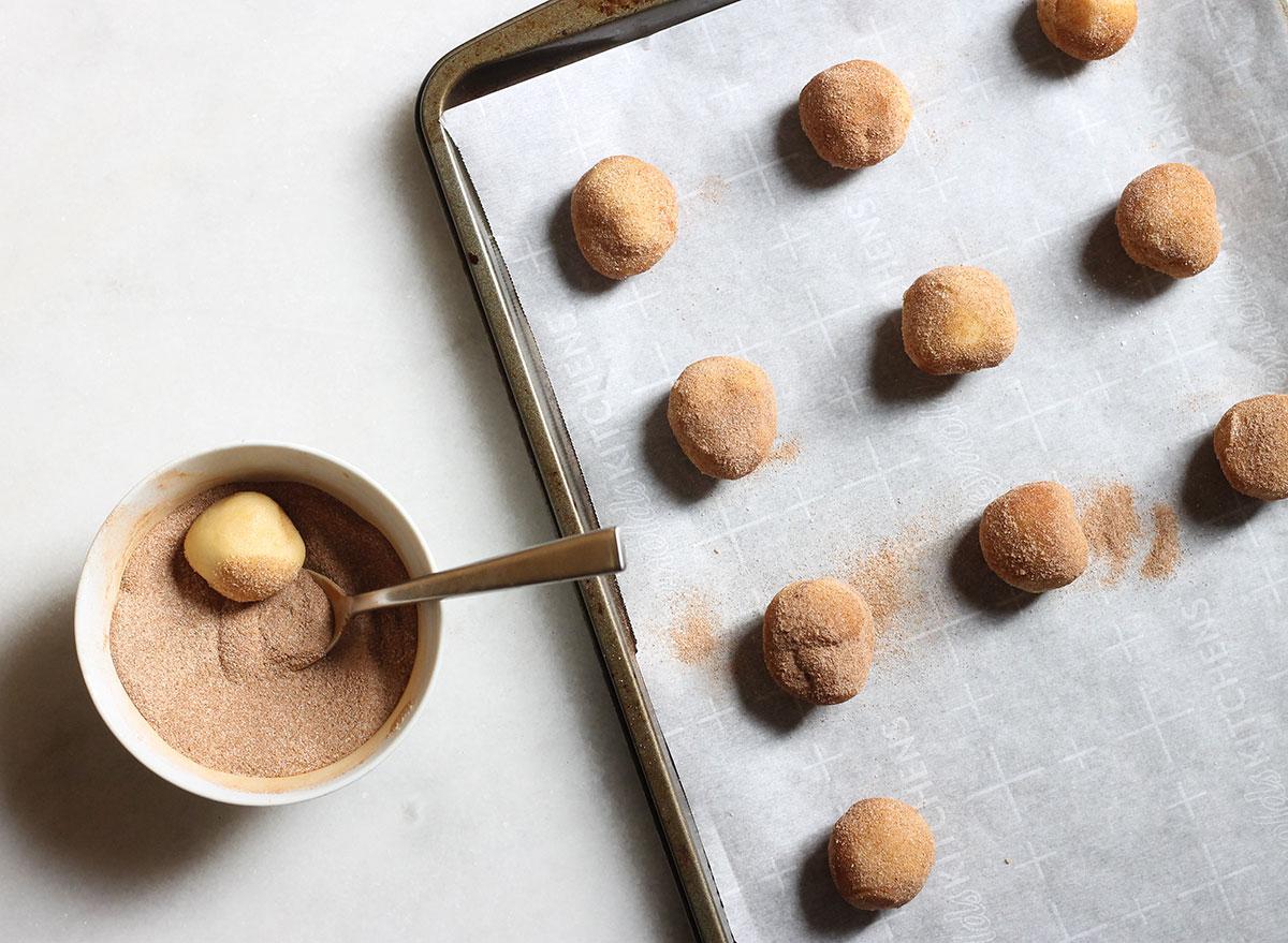 rolling snickerdoodle cookie dough into cinnamon sugar