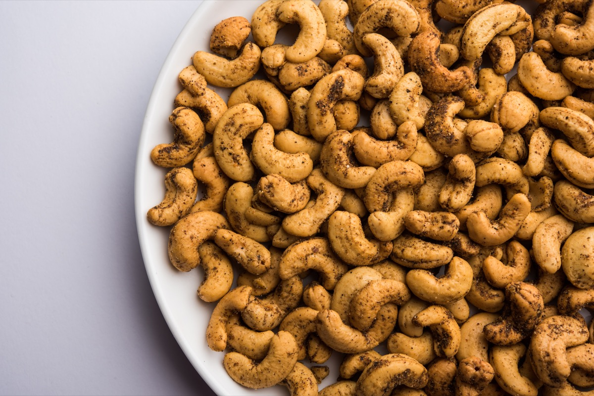spiced cashews in a white ceramic bowl against a grey background