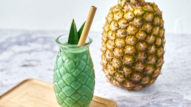 spirulina pina colada smoothie with pineapple in background