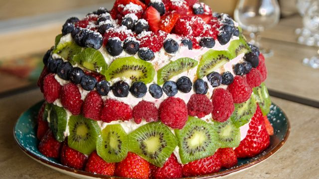 sponge cake topped with raspberries blueberries and kiwi