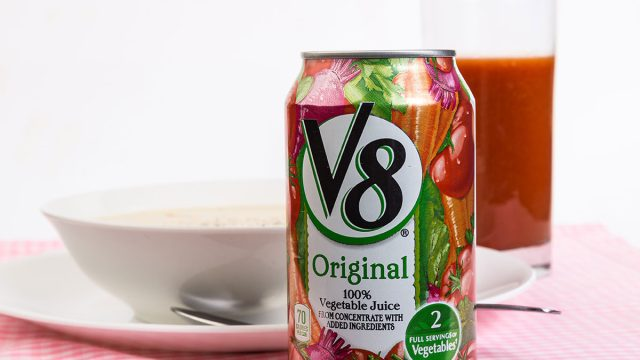 v8 can juice poured into glass cup next to white bowl
