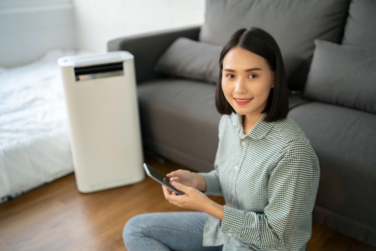 Air purifier , Asian Business woman working with laptop use phone with filter for clean room in a living room