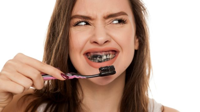 young woman brushing her teeth with a black tooth paste with active charcoal, and black tooth brush
