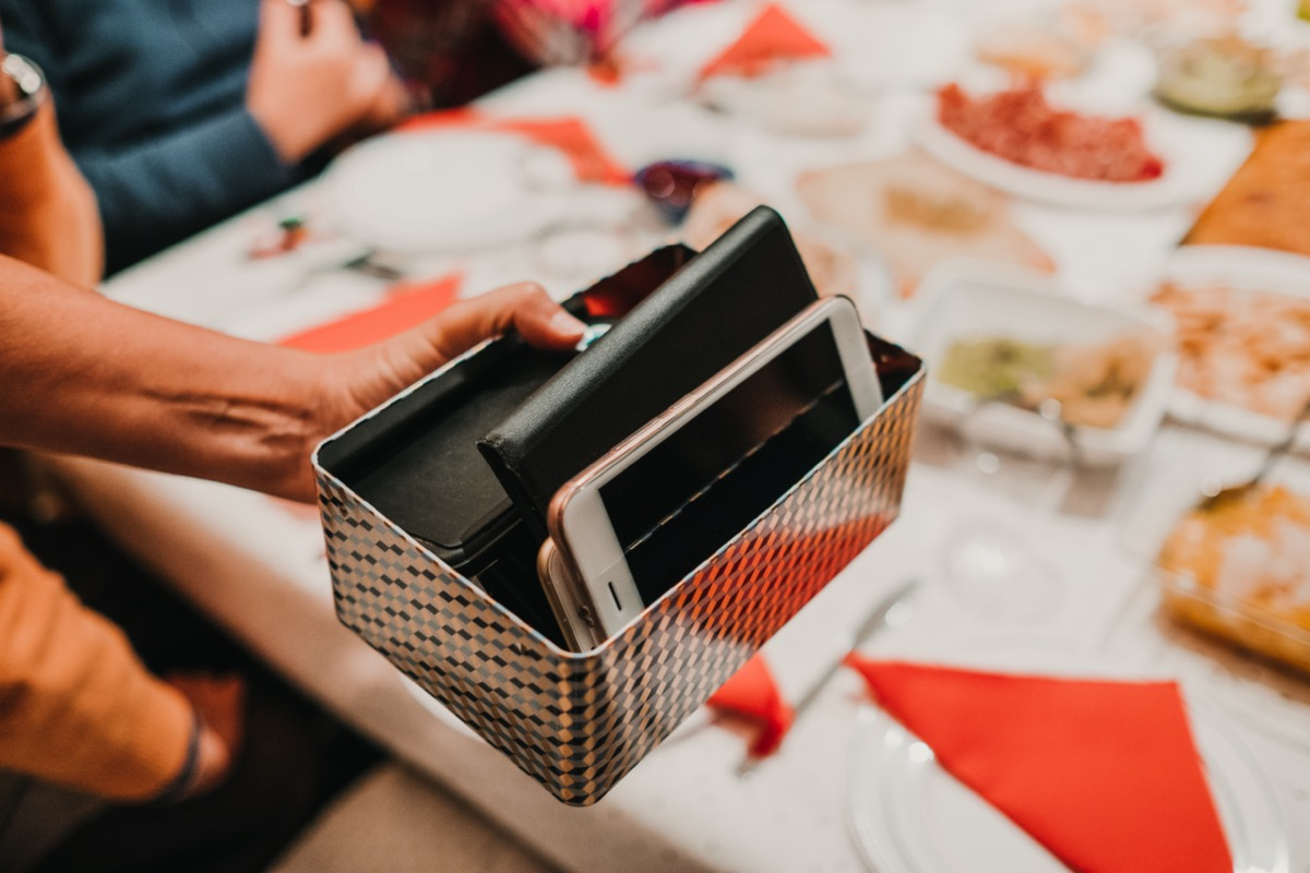 Hand of a woman holding a box full of smartphones of the guests at her dinner. They take a break with technology to have an endearing conversation. Lifestyle.