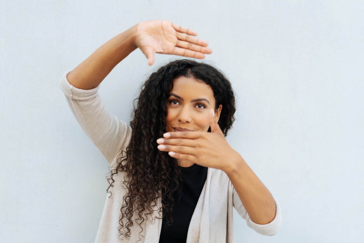 Young woman making a frame gesture with her hands as she visualises a new project standing against a white wall