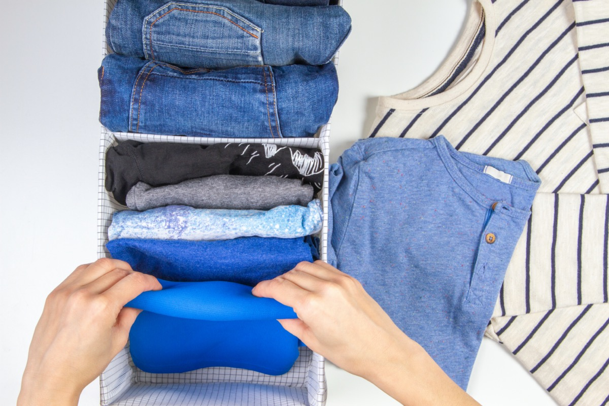 Woman hands tidying up clothes in basket