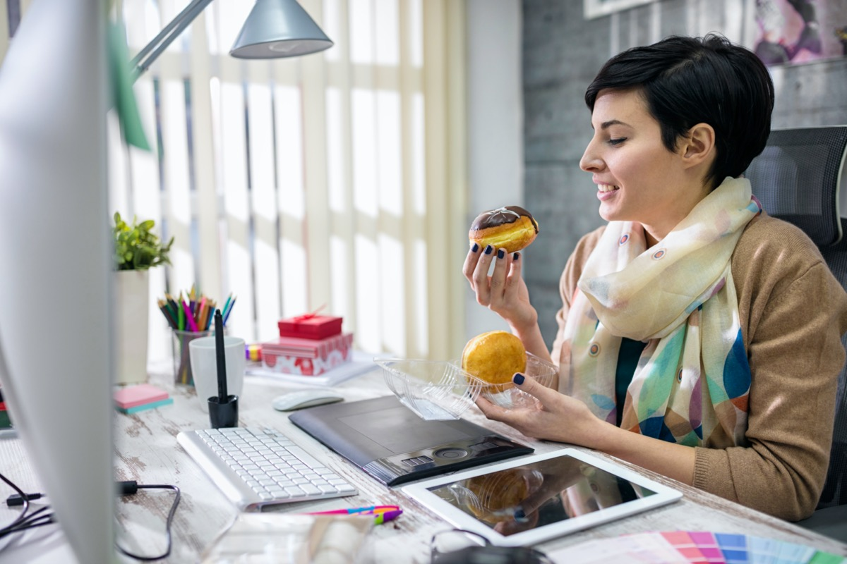 satisfied designer eating donuts in office