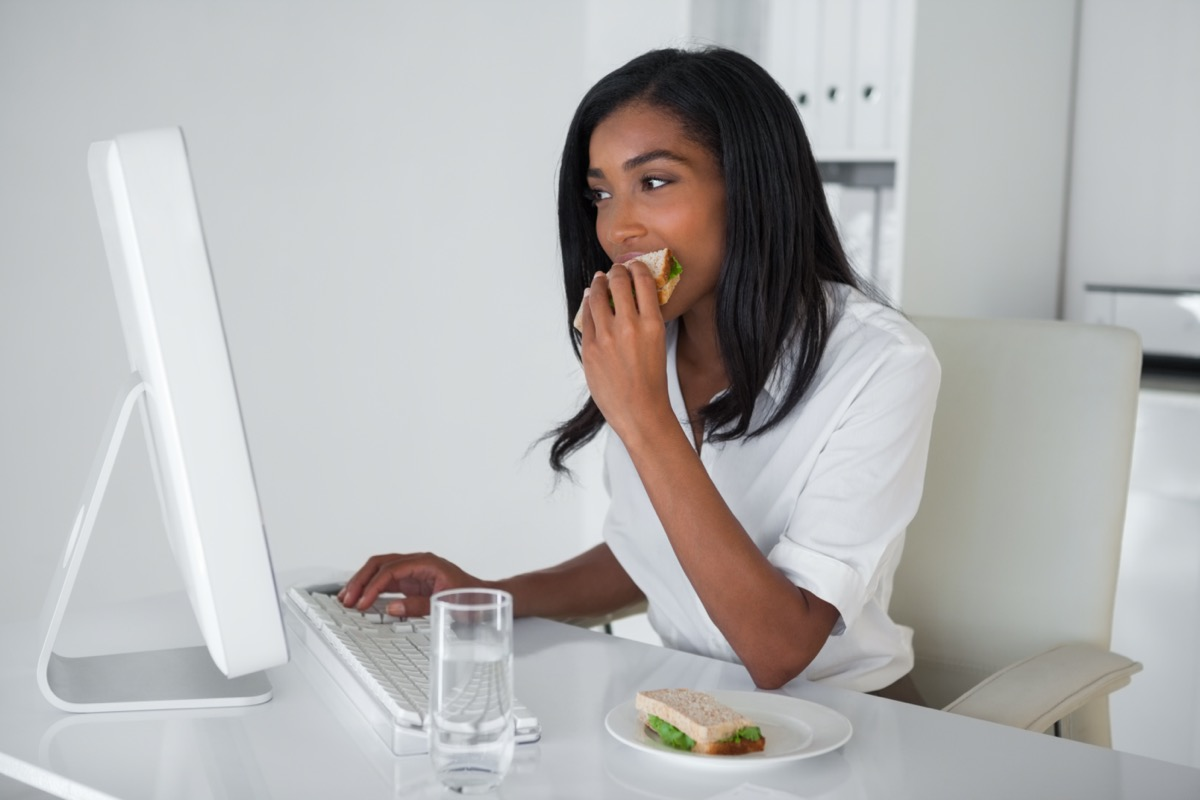 businesswoman eating a sandwich at her desk in her office