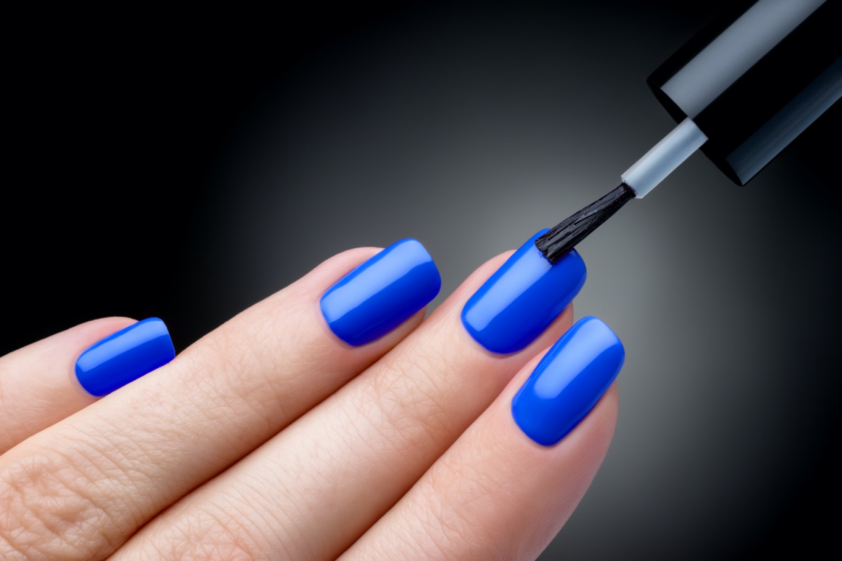 Nail polish being applied to hand, polish is a blue color