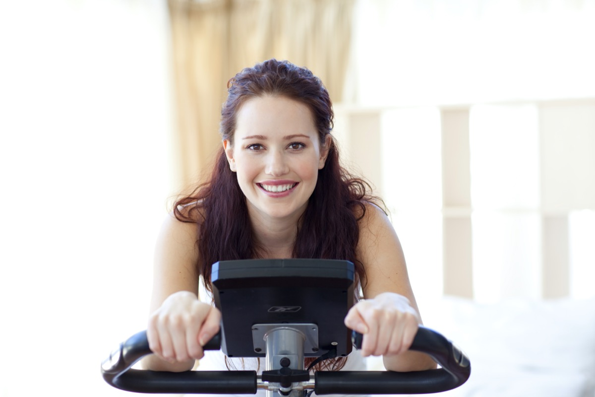 Smiling woman doing spinning in her bedroom at home