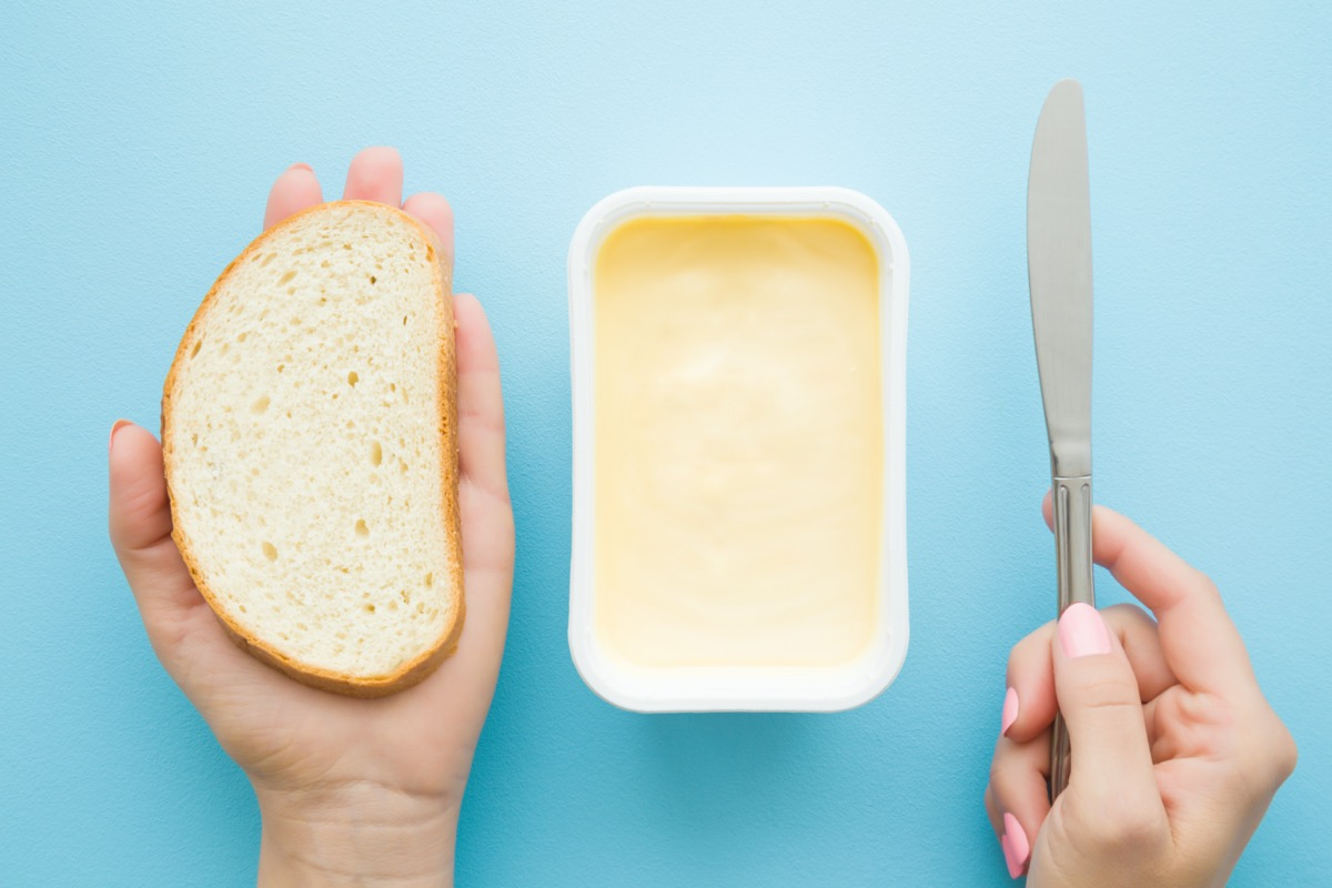 Woman's hands holding slice of white bread and knife. Opened plastic pack of light yellow margarine on pastel blue desk