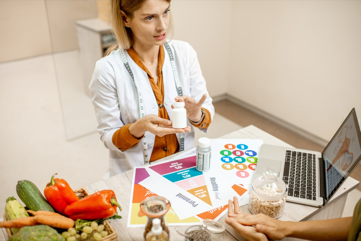 Nutritionist with young woman client talking about meal plan and healthy products during a medical consultation in the office