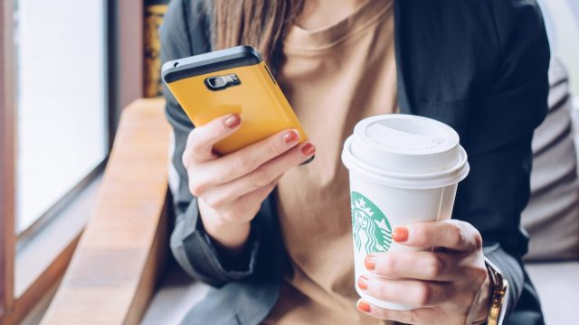 woman holding a cell phone in one hand and a grande starbucks beverage in the order