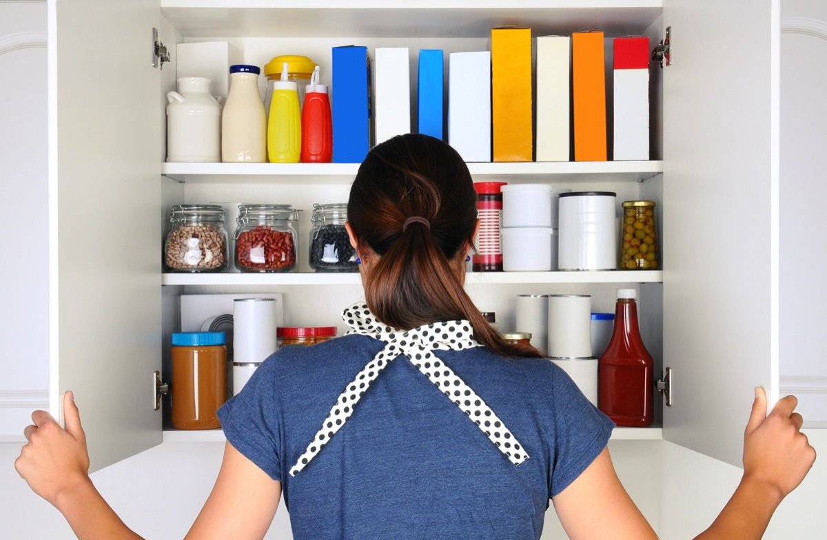 A woman seen from behind opening the doors to a fully stocked pantry. The cupboard is filled with various food stuff and groceries all with blank labels
