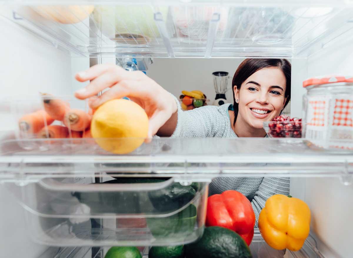 Woman reaching into fridge to grab healthy food lemon