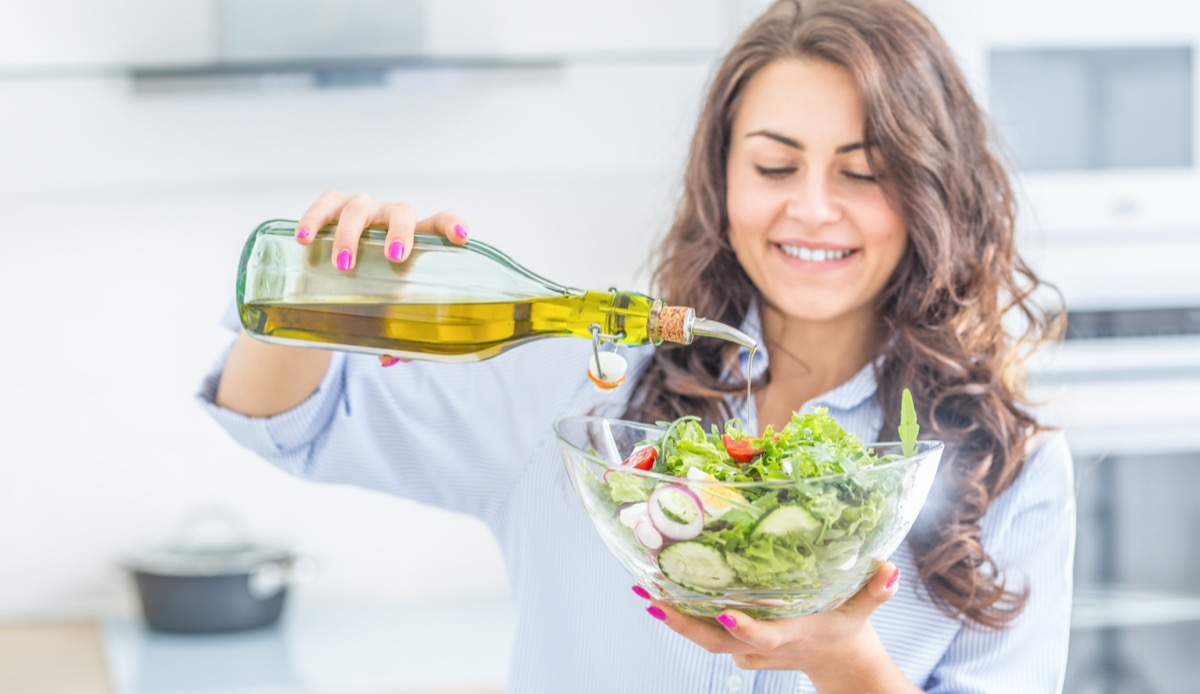 woman pouring olive oil in to the salad. Healthy lifestyle eating concept