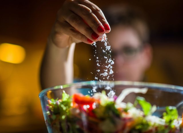 Woman preparing healthy salad in kitchen, adding salt to the bowl