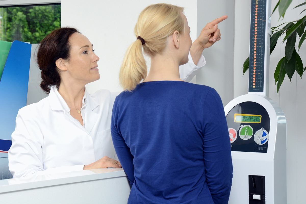 Woman as a patient in pharmacy or doctor's office measures weight and body fat on scales