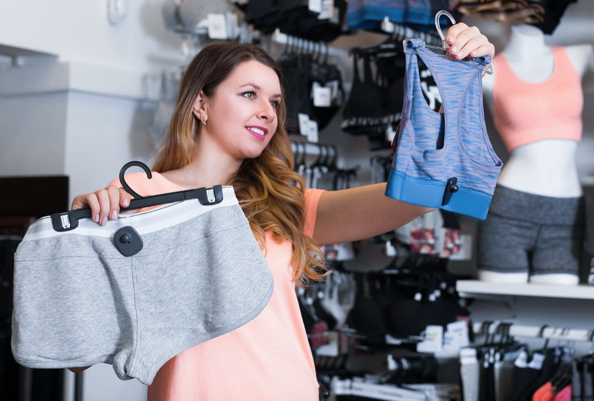 woman client choosing sports clothes in underwear