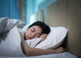 Asian woman sleeping in a bed in a dark bedroom