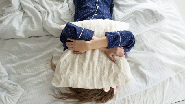 woman covers her face with a pillow