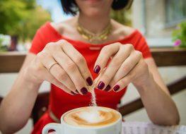 Female hand poured sugar into coffee, cappuccino