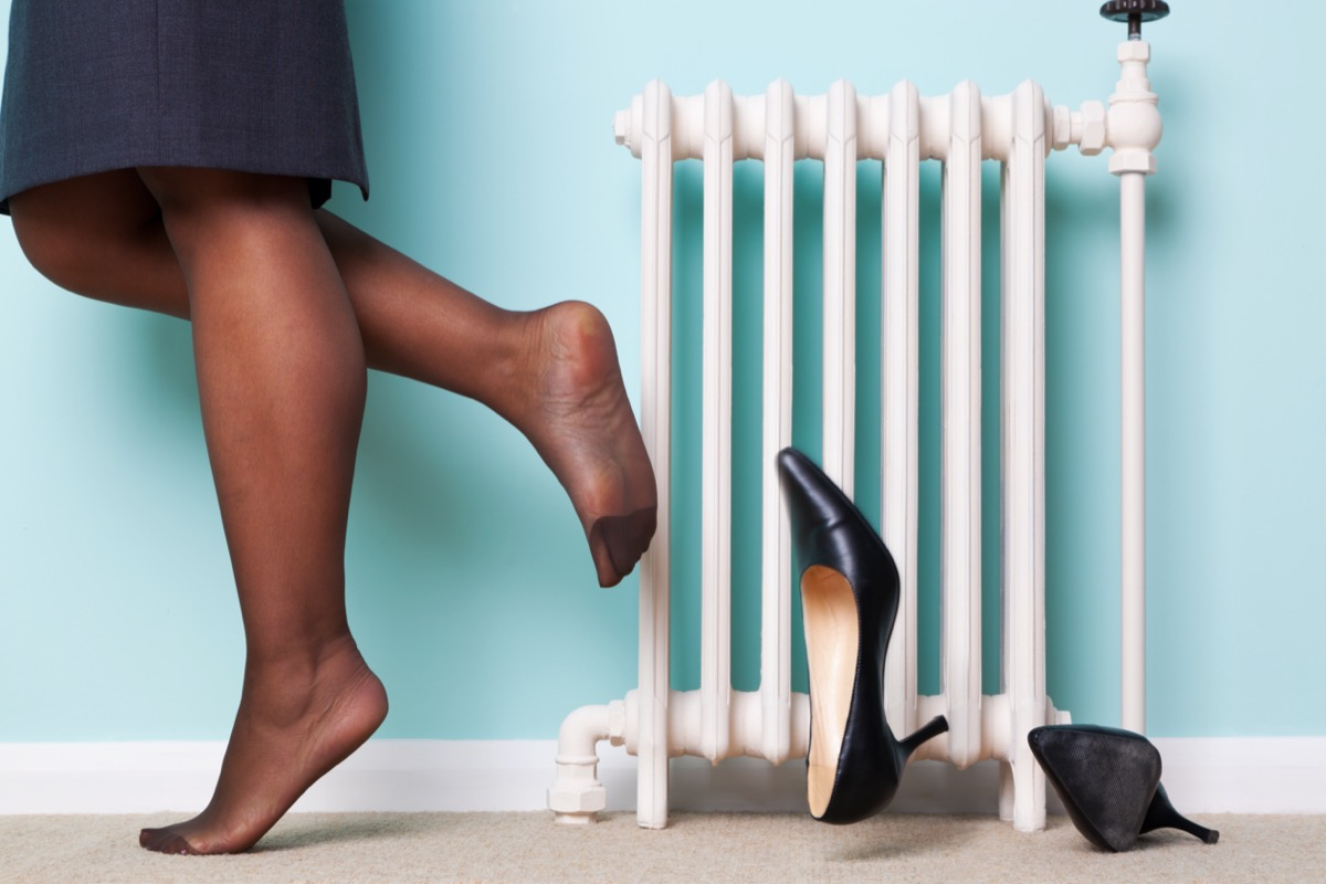 businesswomans legs with stockings on kicking her high heel shoes off as she returns home after a hard day at work