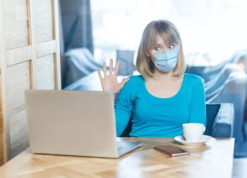 woman with surgical medical mask is sitting and working on laptop and greeting on video call conference