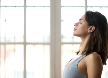 woman in sportswear with eyes closed training in fitness studio, calm fit millennial female practice yoga
