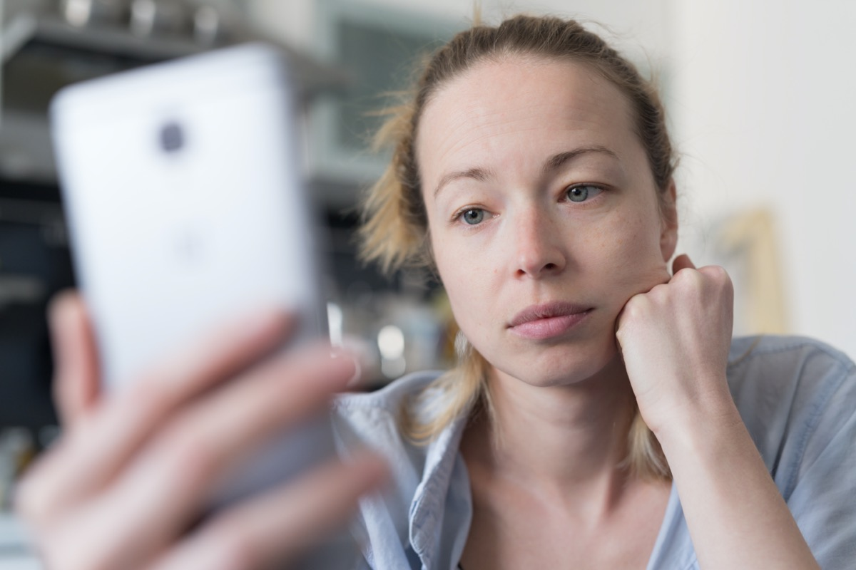Worried woman indoors at home kitchen using social media apps on phone for video chatting and stying connected with her loved ones