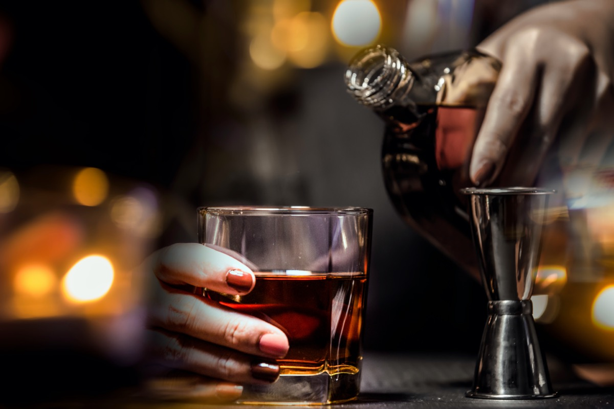 Bartender Serve Whiskey, on wood bar.