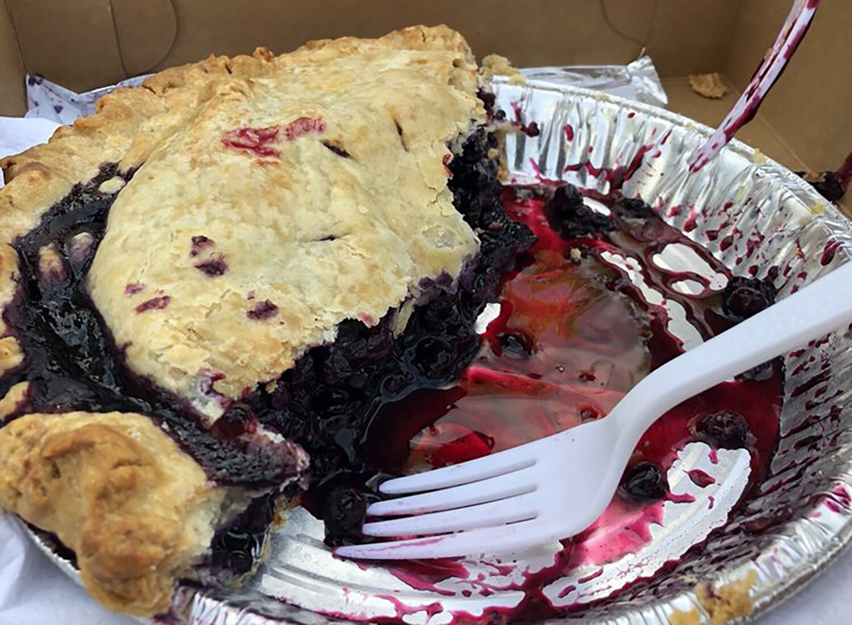 blueberry pie in baking pan with slices removed