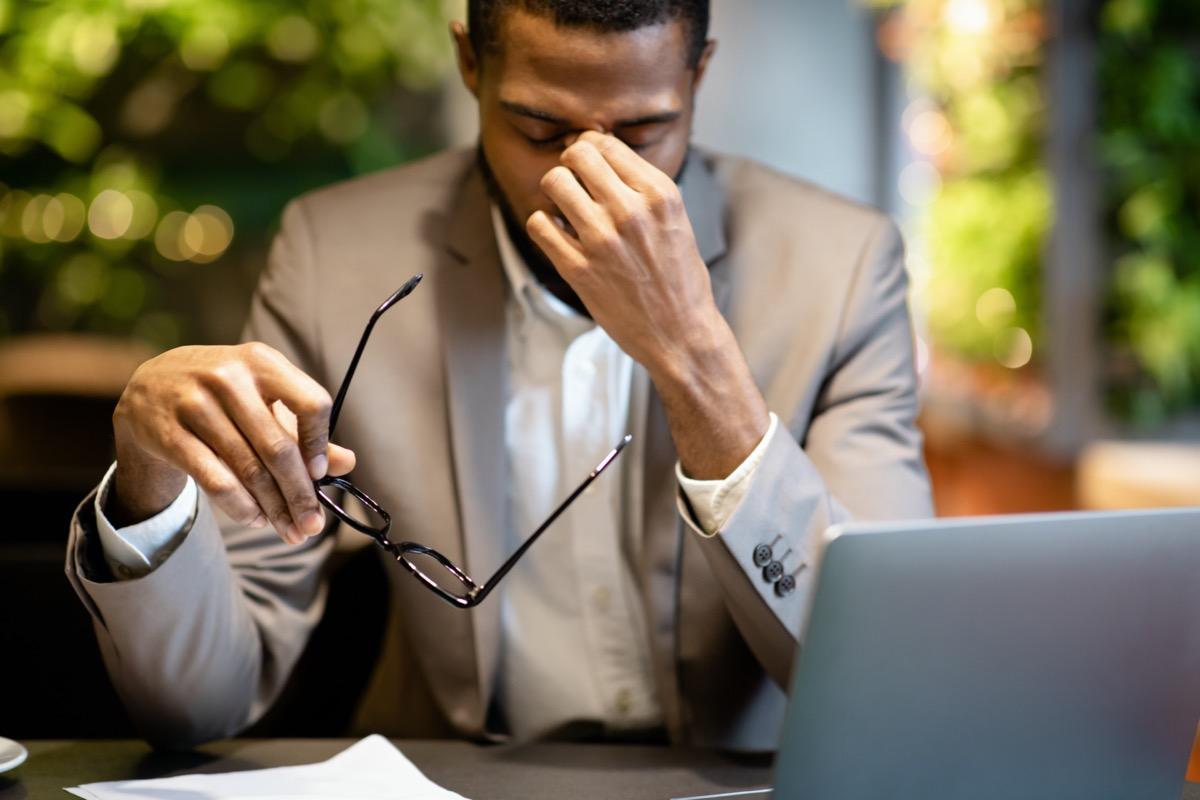 Tired Of Work. Fatigued black businessman taking off glasses, massaging nose, working in cafe