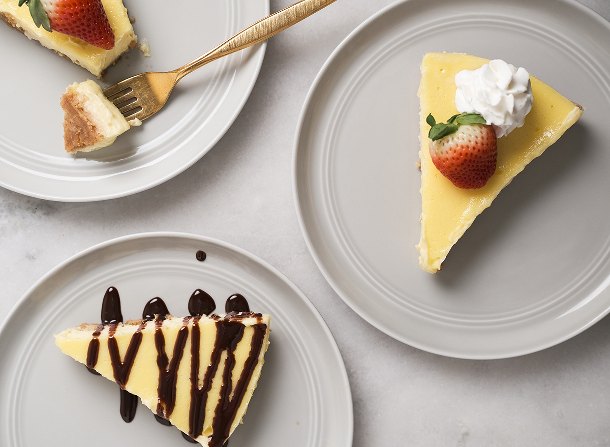 slices of cheesecake with strawberries whipped cream and chocolate sauce on grey plates