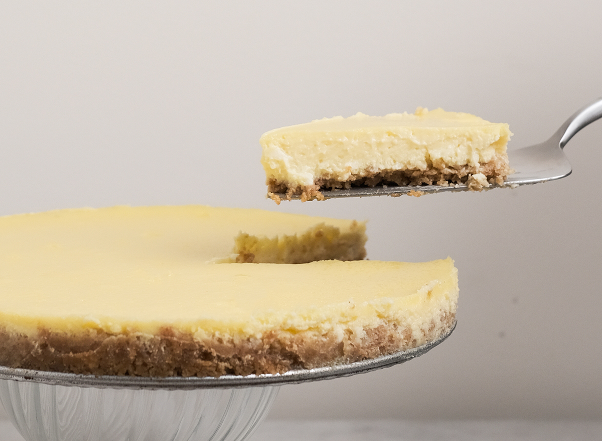 slice of cheesecake lifted from cheesecake platter