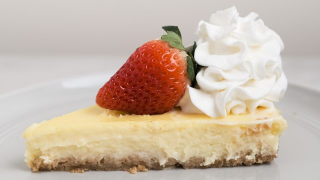slice of copycat cheesecake factory cheesecake with strawberry and whipped cream