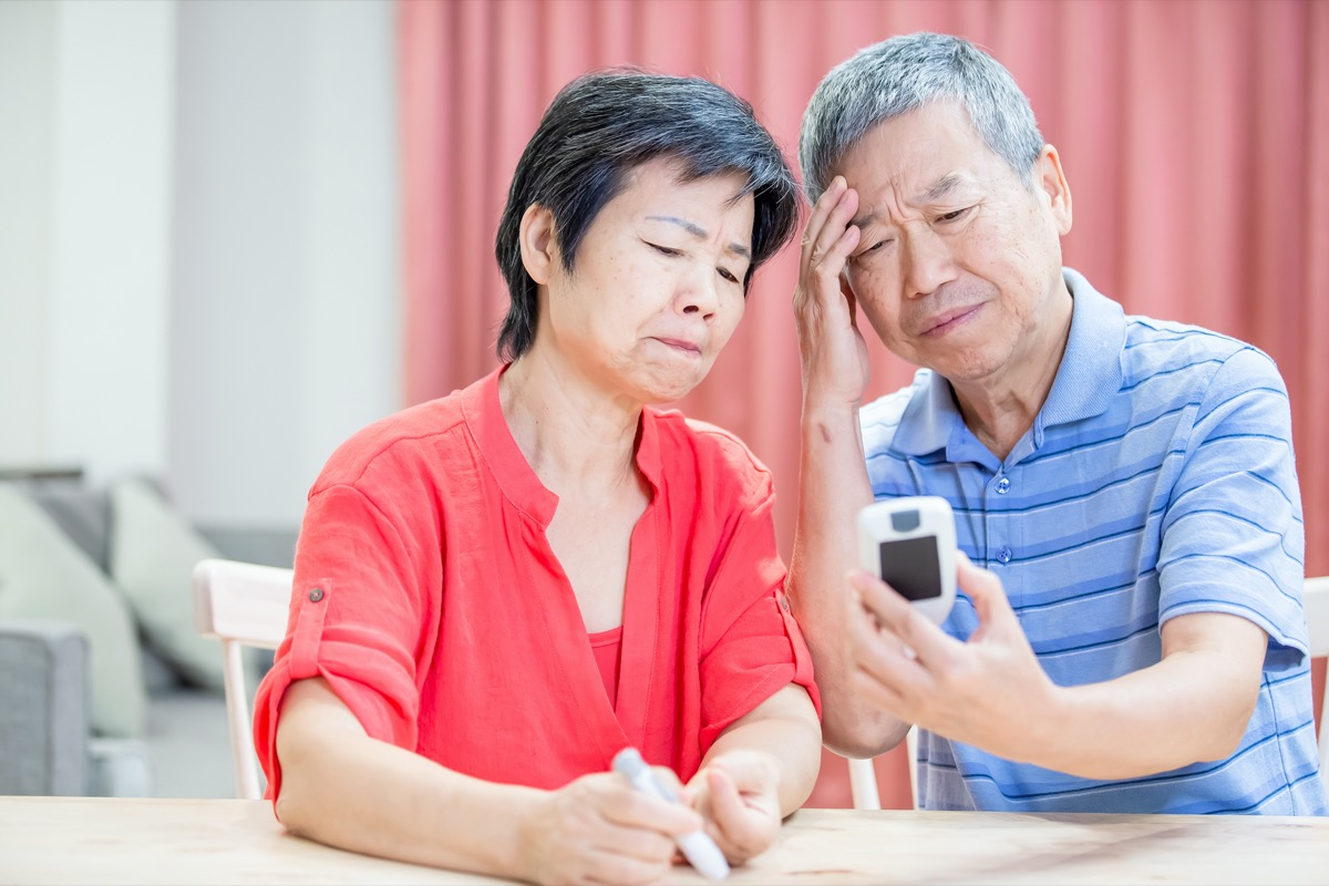 asian elder couple use blood glucose meter and worry about it