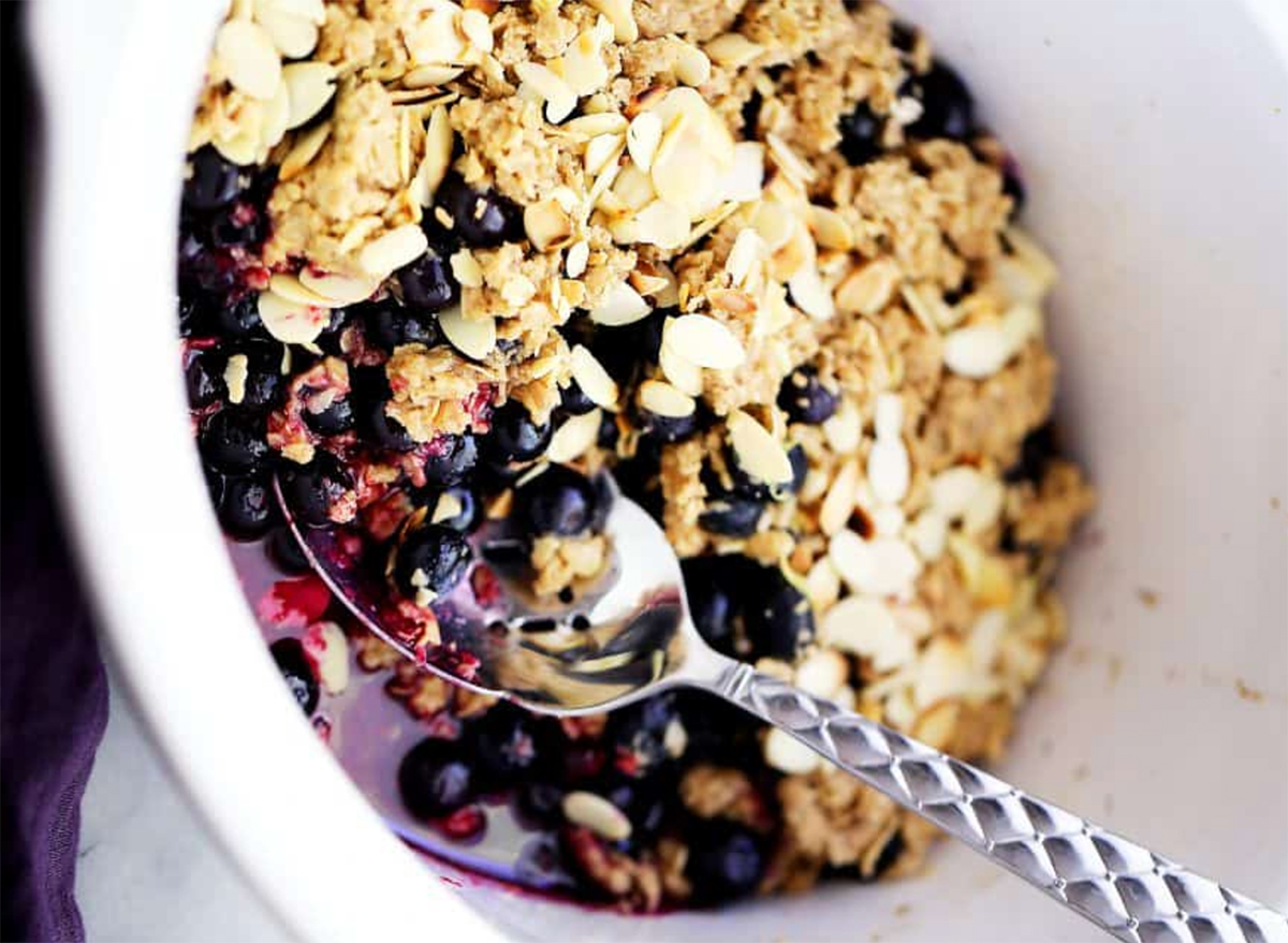 crock pot blueberry crisp in bowl with spoon