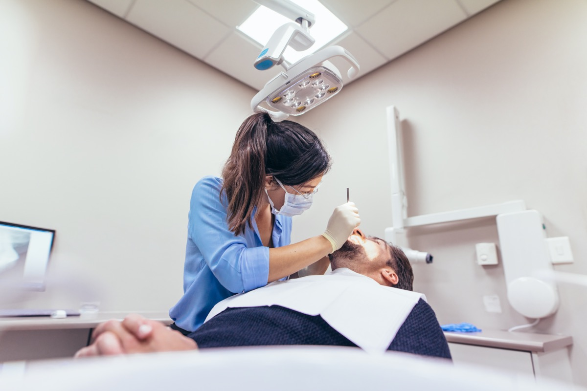 Female dentist examining a patient with tools in dental clinic