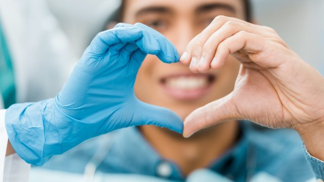selective focus of heart shape hands of dentist and african american patient