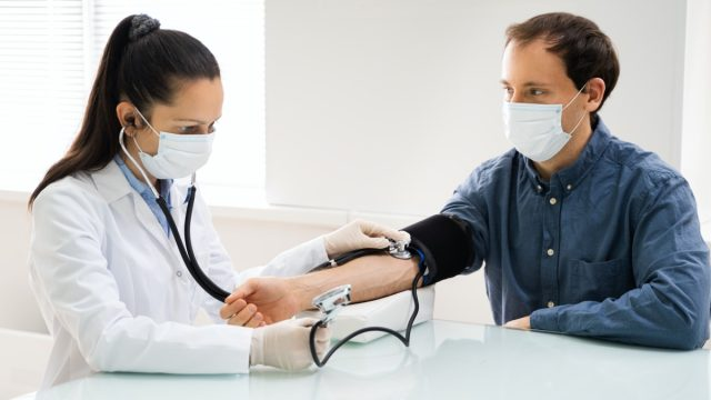 Doctor Checking High Blood Pressure In Face Mask